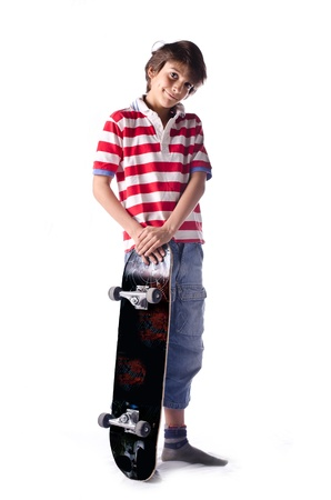Cute young boy standing on white background with skateboard photo