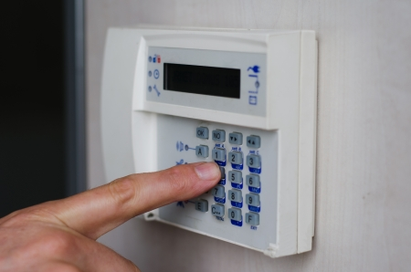 home security system: Finger setting security alarm, pressing keys on keypad