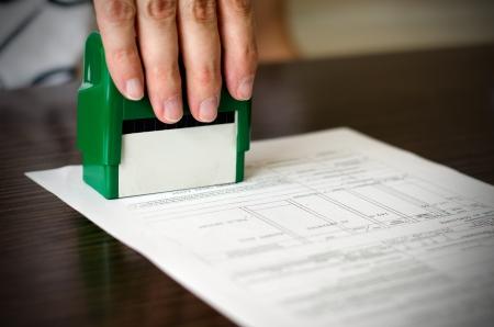Male hand pressing rubber stamp on document. Dark desktop underneath