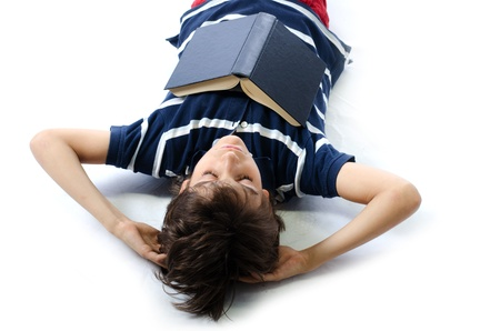 Cute boy on the floor sleeping with school book, isolated on white  photo