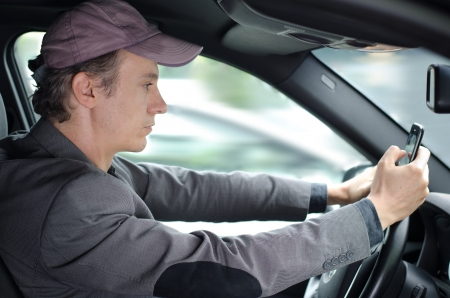 Vezető férfi a kocsijában használja, vagy gépelés sejt mobiltelefon, veszélyes helyzet