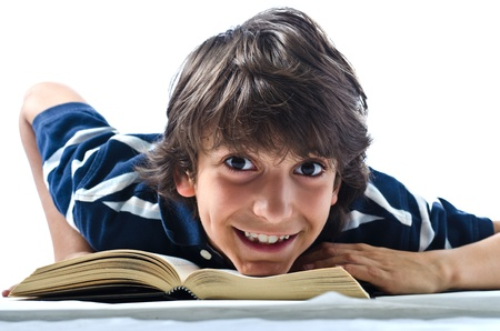 Smiling and cheerful boy reading and studying school book