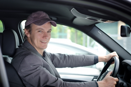 Handsome young man driving his car and smiling