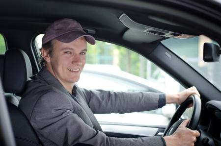 Jóképű fiatalember vezetői a kocsiját, és mosolyogva Stock fotó