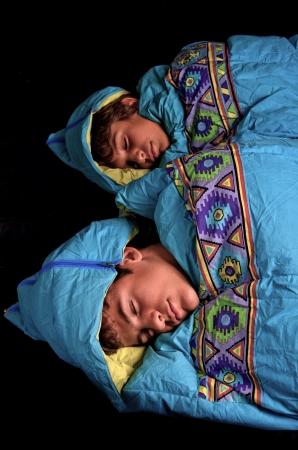 Two young boys sleep in sleeping bags