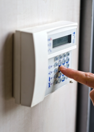 home security system: Finger pressing keys on alarm keypad