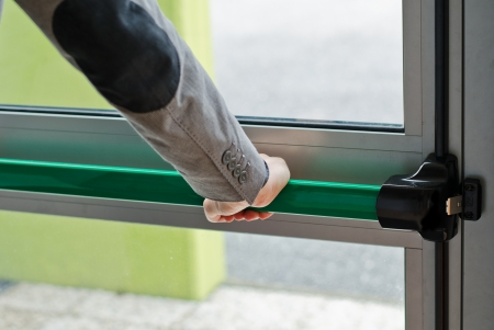 Hand pressing panic push bar to open door in case of emergency photo
