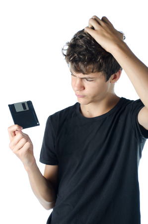 Teenage puzzled with floppy disk in his hand isolated on white