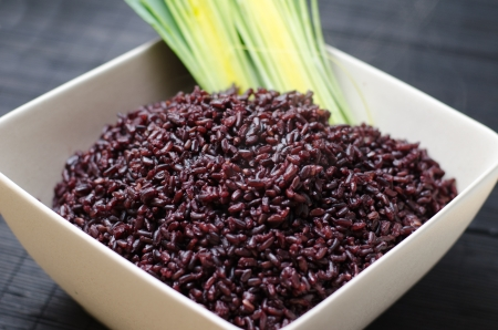 Big bowl of cooked red rice on dark background