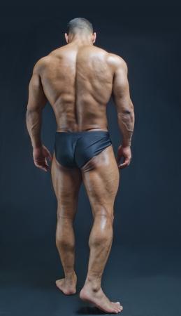 Full back figure of muscular bodybuilder on dark background
