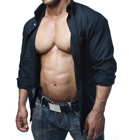 Male bodybuilder in jeans and open shirt revealing really muscular pecs and abs Stock Photo
