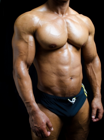 male torso: Shirtless male bodybuilder torso: ripped bicep, arms and pecs on black background