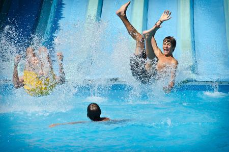 ウォーターパーク、スイミング プールに水しぶきで若い人々 と楽しく水スライドします。