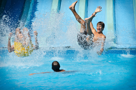 Young people having fun on water slides in aqua park, splashing into swimming pool