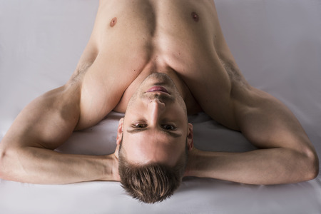 Shirtless young man leaning on white sheet. Hands under his head. Muscular build
