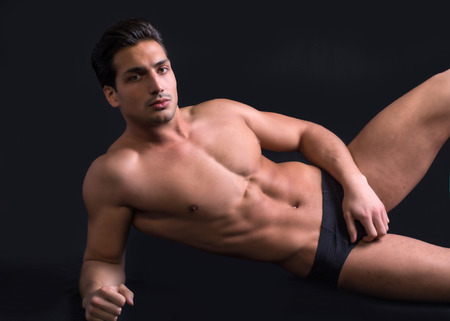 muscular body: Handsome latin young man on floor, wearing only underwear. Muscular build