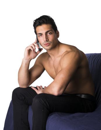 Félmeztelen latin fiatalember segítségével mobiltelefon, ül a kanapén, és nézi kamera. Fehér háttér