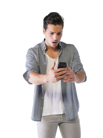 Young man looking at cell phone with angry or surprised expression. Isolated on white background