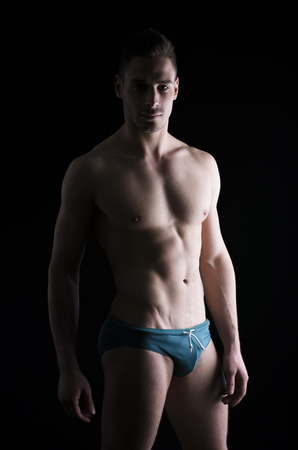 Chiaroscuro photo of shirtless young man standing on black backdrop, wearing underwear photo