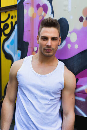 tanktop: Young man against bright colored graffiti wall wearing white tanktop