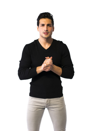 Brown eyed, black haired latin man standing on white background. Hands joined together Standard-Bild