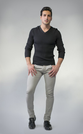 Full body photo of young man standing on grey background. Casual clothes photo