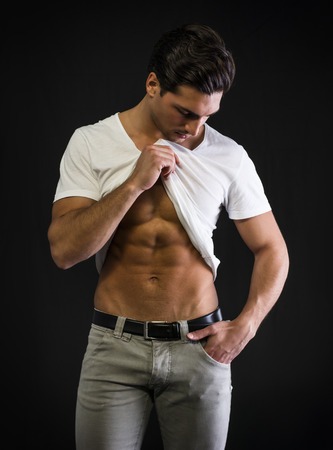 Young man with muscular body pulling up t-shirt on ripped abs photo
