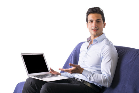 Young man showing laptop computer sitting on couch. Pure white background photo