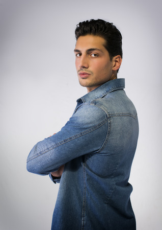 Profile shot of young man wearing denim shirt, arms crossed on chest photo