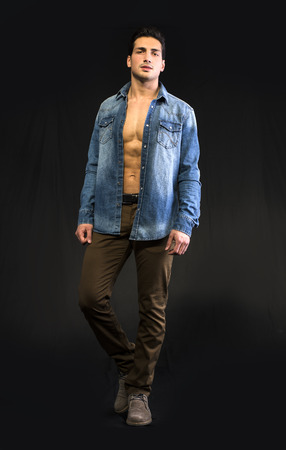 Young man wearing denim shirt open on chest. Full body shot photo