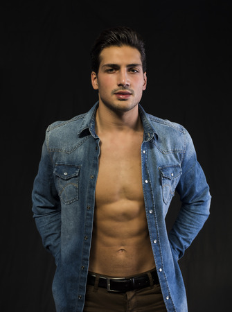 Latin young man with open denim shirt on naked chest. Muscular build photo
