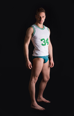 man underwear: Athletic young man wearing basketball shirt and underwear on black background Stock Photo