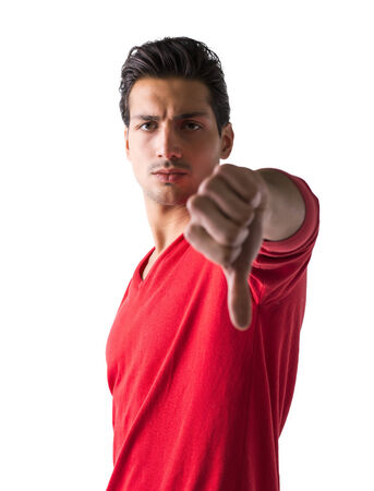 Handsome young man doing thumb down sign, while looking at camera with stern expression, isolated