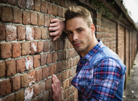 Young man leaning on old brick wall, wearing blue and red shirt photo