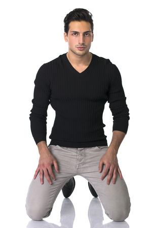 Jó kinézetű fiatalember térdre a földre, elszigetelt fehér Stock fotó