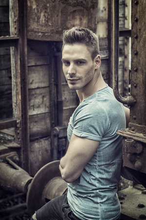 A handsome young man outdoor, sitting on rusty and old train, looking at camera thinking