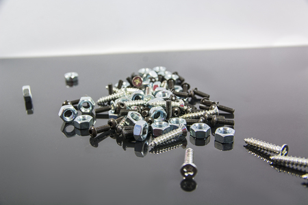 bolts and nuts: Close-up of heap of bolts, screws and nuts on neutral background in studio shot