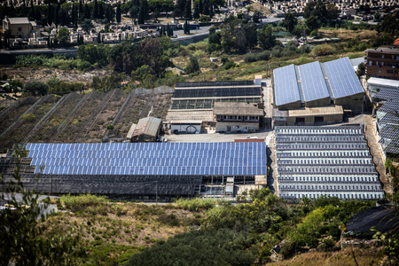Greenhouse and factory with solar panels on roof, aerial view