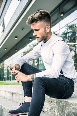 Stylish trendy young man using cell phone, outdoor next to office window, looking confident away Reklamní fotografie