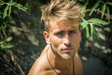 Head and shoulders shot of shirtless blond young man seen from above, looking at camera 免版税图像