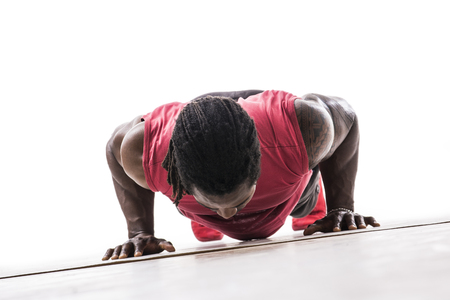 Unrecognizable black young man in studio doing push-ups on the floor. Tilted shot