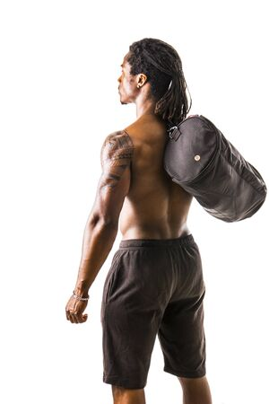 Shirtless muscular black young man with gym bag on shoulder, shot from behind in studio shot isolated on white Stock Photo