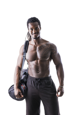 physique: Shirtless muscular black young man with gym bag on shoulder, shot from behind in studio shot isolated on white Stock Photo