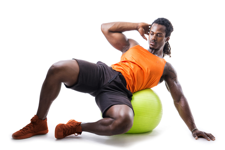 fitball: Muscular man holding inflatable fitness ball, looking at camera, leaning on it isolated on white background Stock Photo