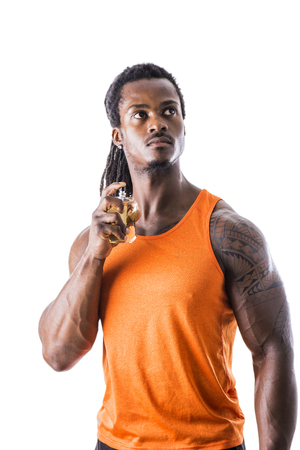 Black muscular male model spraying cologne, isolated on white background