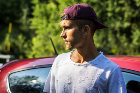 Portrait of young attractive blond man with baseball cap and white t-shirt, next to his new stylish car outdoor in countryside Stock fotó