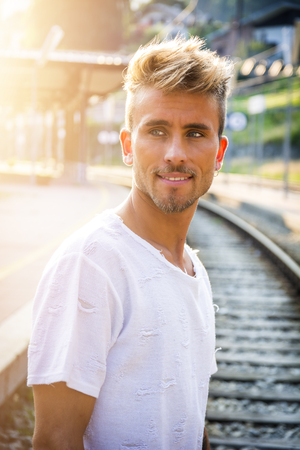 Attractive blond young man standing on railroad tracks, wearing white t-shirt, looking away Stock fotó