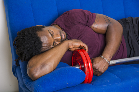Young strong black male sleeping on couch embracing barbell. Stock fotó
