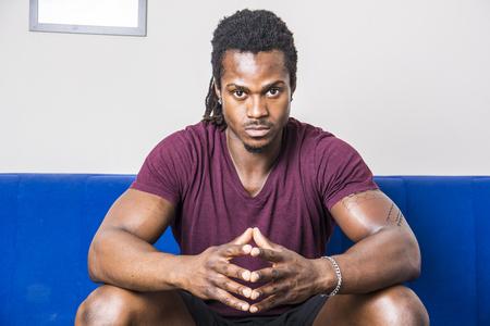 ハンサムな筋肉黒人男性、自宅でソファの上に座ってカメラを自信を持って探して 写真素材