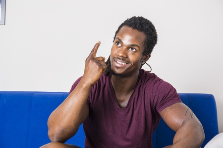 Handsome black young man thinking an idea, doing funny expression and pointing finger up